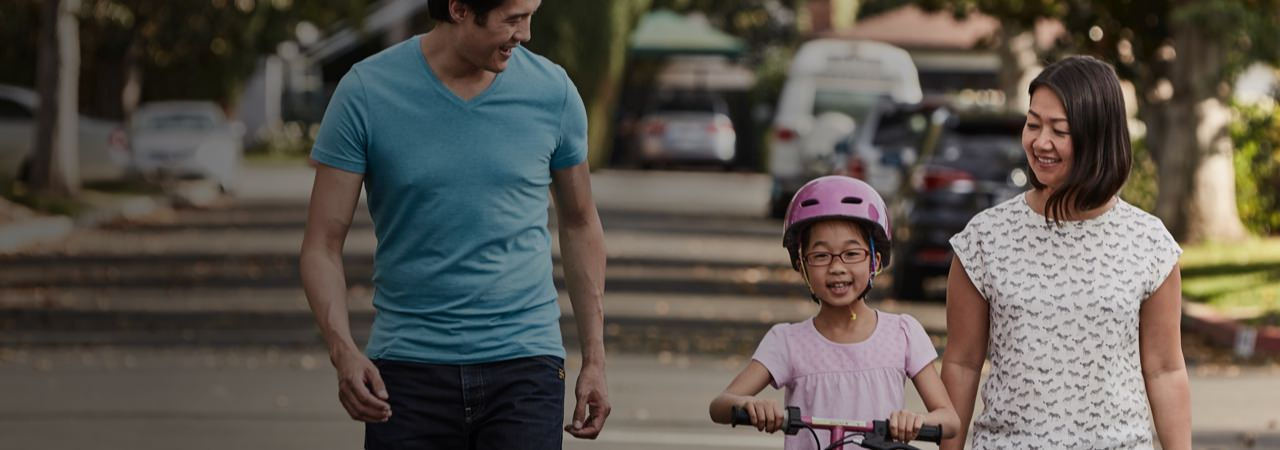 Man and woman walking in a bike while their child is riding their bile beside them.